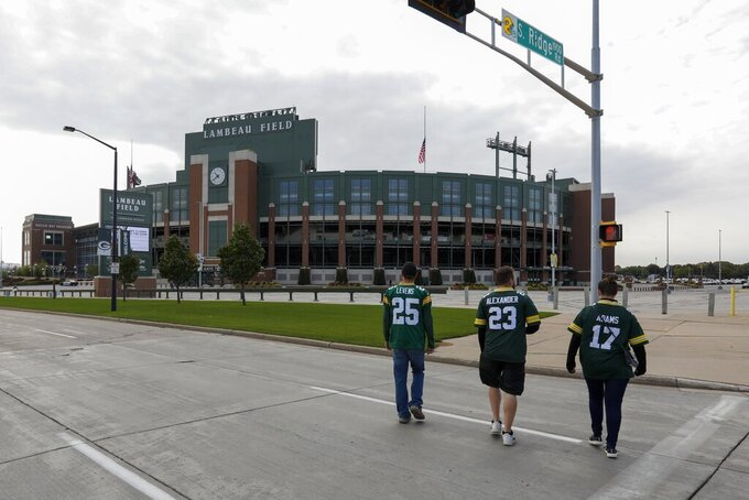 Fans walk on the street outside Lambeau Field before an NFL football game between the Green Bay Packers and the Detroit Lions Sunday, Sept. 20, 2020, in Green Bay, Wis. (AP Photo/Mike Roemer)