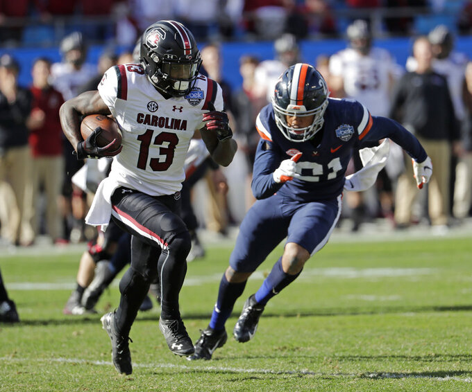 South Carolina's Shi Smith (13) runs as Virginia's Juan Thornhill (21) chases during the first half of the Belk Bowl NCAA college football game in Charlotte, N.C., Saturday, Dec. 29, 2018. (AP Photo/Chuck Burton)