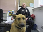In this Jan. 24, 2020, photo, Sammy, a police dog, sits in the lobby of the Fair Haven police station with Sergeant Dale Kerber, in Fair Haven, Vt. Sammy is running for honorary mayor of the town against an incumbent goat as a playground fund-raiser. (AP Photo/Lisa Rathke)