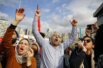 Protesters chant slogans during ongoing protests against the Lebanese political class, in front of a Finance Ministry building in Beirut, Lebanon, Friday, Nov. 29, 2019. Protesters have been holding demonstrations since Oct. 17 demanding an end to widespread corruption and mismanagement by the political class that has ruled the country for three decades. (AP Photo/Bilal Hussein)