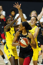 Las Vegas Aces center A'ja Wilson (22) is blocked by Seattle Storm forward Natasha Howard (6) and forward Breanna Stewart (30) during the first half of Game 3 of basketball's WNBA Finals Tuesday, Oct. 6, 2020, in Bradenton, Fla. (AP Photo/Chris O'Meara)