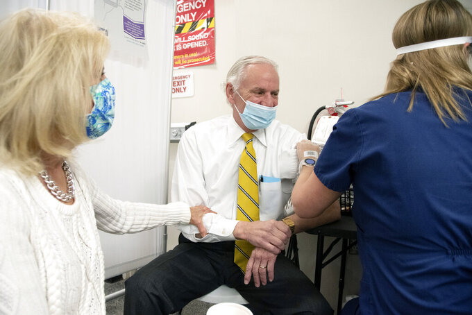 In this photo provided by the South Carolina Governor's Office, South Carolina Gov. Henry McMaster receives his first dose of the Pfizer COVID-19 vaccine at a CVS pharmacy in Columbia, S.C., as his wife first lady Peggy McMaster holds his arm on Monday, April 19, 2021.   (Ryan Flynn/South Carolina Governor's Office via AP)