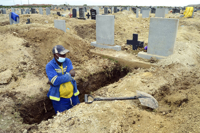 A grave digger prepares graves at the Motherwell Cemetery in Port Elizabeth, South Africa, Friday, Dec. 4, 2020. Health Minister Zweli Mkhize announced on Wednesday, Dec. 9, 2020 that the country is now experiencing a Covid-19 pandemic second wave. (AP Photo/Theo Jeftha)