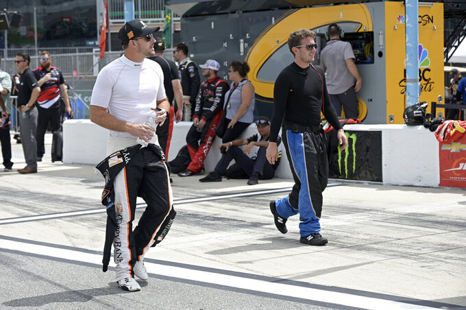 Driver Daniel Hemric (18), left, walks to his vehicle on pit road before a NASCAR Xfinity Series auto race at Daytona International Speedway, Saturday, Aug. 28, 2021, in Daytona Beach, Fla. (AP Photo/Phelan M. Ebenhack)