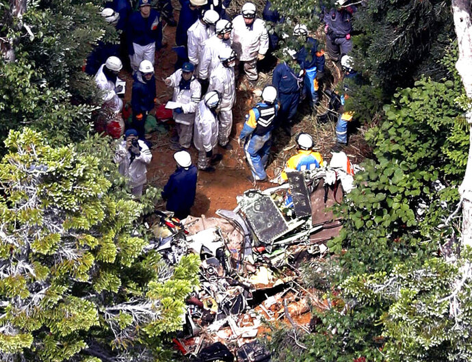 Investigators work near the wreckage of a Japanese search and rescue helicopter that crashed into the central mountains in Nakanojo, Gunma prefecture, northwest of Tokyo Saturday, Aug. 11, 2018. All nine people aboard the helicopter were confirmed dead Saturday, authorities said. (Kyodo News via AP)
