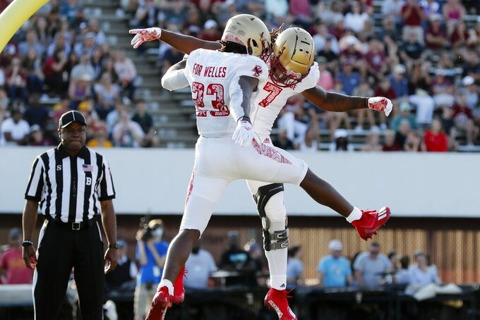 Boston College running back Travis Levy (23) celebrates his touchdown with wide receiver Kobay White (7) during the second half of an NCAA college football game against Massachusetts, Saturday, Sept. 11, 2021, in Amherst, Mass. (AP Photo/Michael Dwyer)