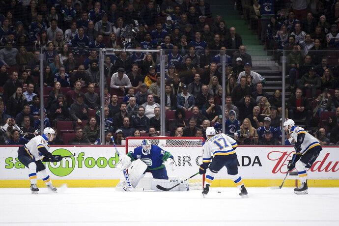 St. Louis Blues' Jaden Schwartz (17) scores against Vancouver Canucks goalie Jacob Markstrom (25), of Sweden, as St. Louis' Brayden Schenn (10) and Alex Pietrangelo (27) watch during overtime in an NHL hockey game Tuesday, Nov. 5, 2019, in Vancouver, British Columbia. (Darryl Dyck/The Canadian Press via AP)