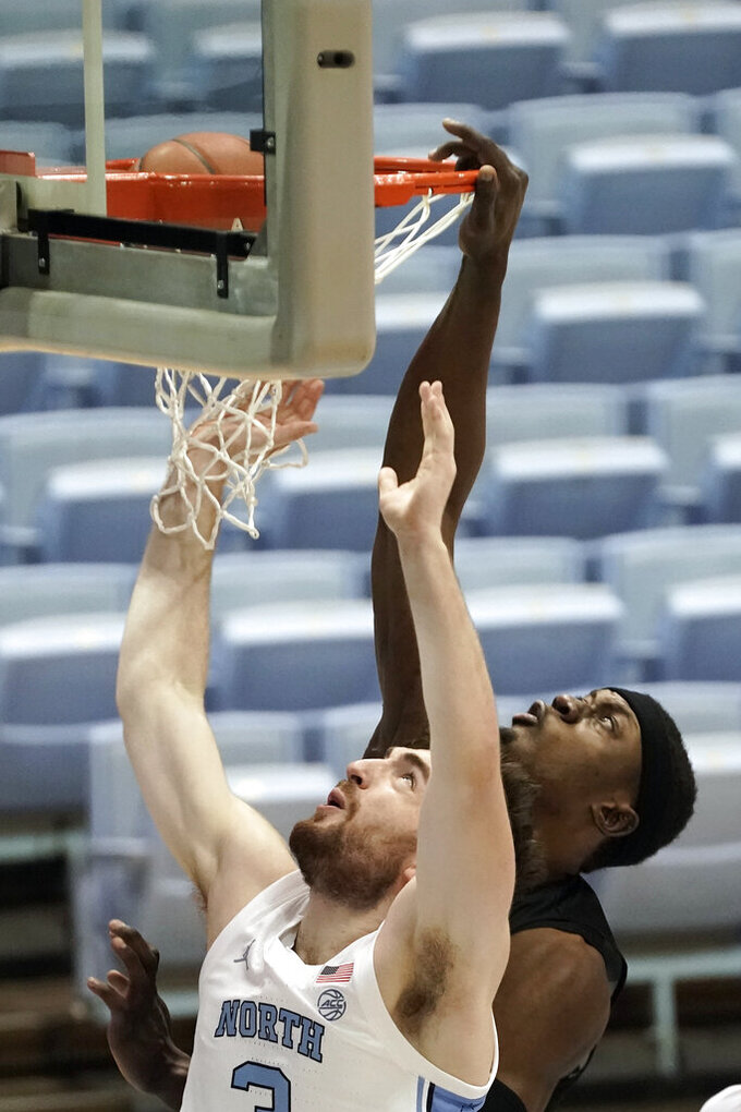 North Carolina guard Andrew Platek is fouled by North Carolina Central forward Nehemie Kabeya, right, during the first half of an NCAA college basketball game in Chapel Hill, N.C., Saturday, Dec. 12, 2020. (AP Photo/Gerry Broome)