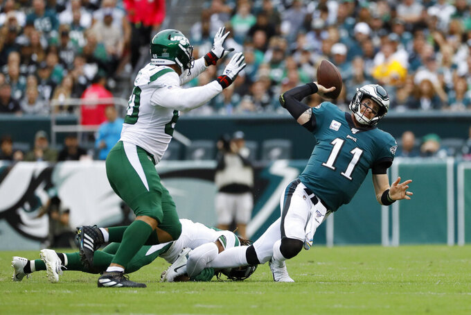 Philadelphia Eagles' Carson Wentz, right, passes the ball as he is tackled by New York Jets' Darryl Roberts, center, as Jordan Willis defends during the first half of an NFL football game, Sunday, Oct. 6, 2019, in Philadelphia. (AP Photo/Michael Perez)