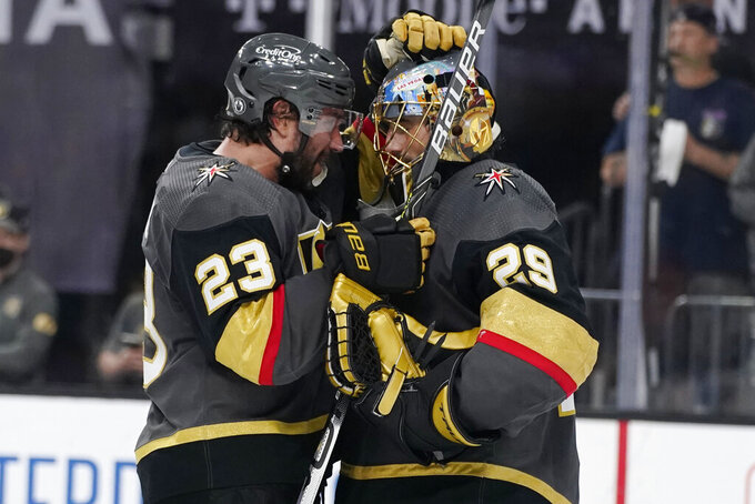 Vegas Golden Knights defenseman Alec Martinez (23) and goaltender Marc-Andre Fleury (29) celebrate after defeating the Colorado Avalanche in Game 6 of an NHL hockey Stanley Cup second-round playoff series Thursday, June 10, 2021, in Las Vegas. (AP Photo/John Locher)