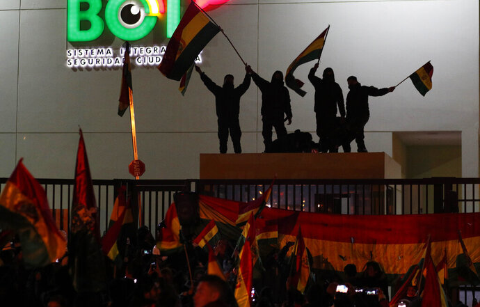 Police officers standing on the rooftop of a security booth at a police station wave Bolivian flags in front of protesters in La Paz, Bolivia, Saturday, Nov. 9, 2019. Growing dissension in police ranks posed a new threat to President Evo Morales, who claimed victory after the Oct. 20 vote but has since faced protests in which three people have been killed and hundreds injured. (AP Photo/Juan Karita)