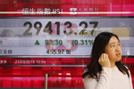 A woman walks past an electronic board showing Hong Kong share index outside a bank in Hong Kong, Thursday, March 21, 2019.  Shares in Asia are mostly higher after the Federal Reserve said it has ruled out interest rate increases for this year.  (AP Photo/Kin Cheung)