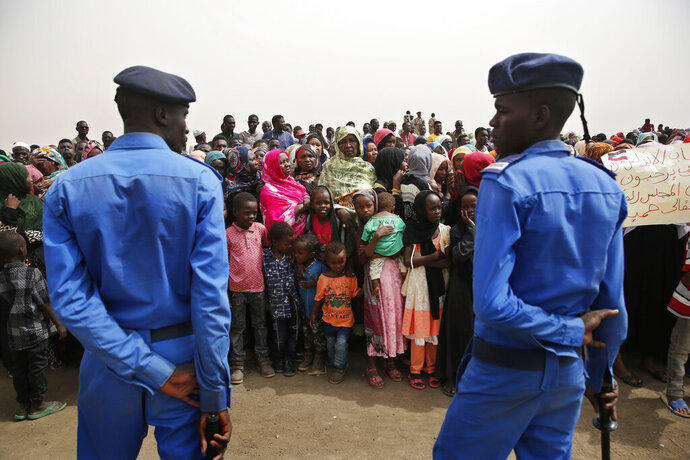 Sudanese policemen stand guard, as supporters of Gen. Mohammed Hamdan Dagalo, the deputy head of the military council, better known as Hemedti, attend a military-backed rally, in Mayo district, south of Khartoum, Sudan, Saturday, June 29, 2019. Sudan's ruling generals say they have accepted a joint proposal from the African Union and Ethiopia to work toward a transitional government. (AP Photo/Hussein Malla)