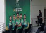 Pakistani police officers observes area next to portraits of Pakistani cricketer from an enclosure of the Pindi Cricket Stadium before the stat of the first one day international cricket match between Pakistan and New Zealand at the Pindi Cricket Stadium, in Rawalpindi, Pakistan, Friday, Sept. 17, 2021. The limited-overs series between Pakistan and New Zealand has been postponed due to security concerns of the Kiwis. (AP Photo/Anjum Naveed)