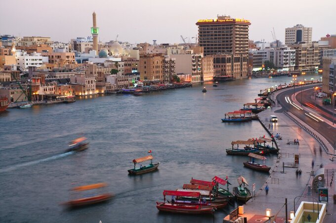In this photograph taken with a slow shutter speed, traditional abra boats navigate the Dubai Creek in Dubai, United Arab Emirates, Wednesday, July 1, 2020. (AP Photo/Jon Gambrell)