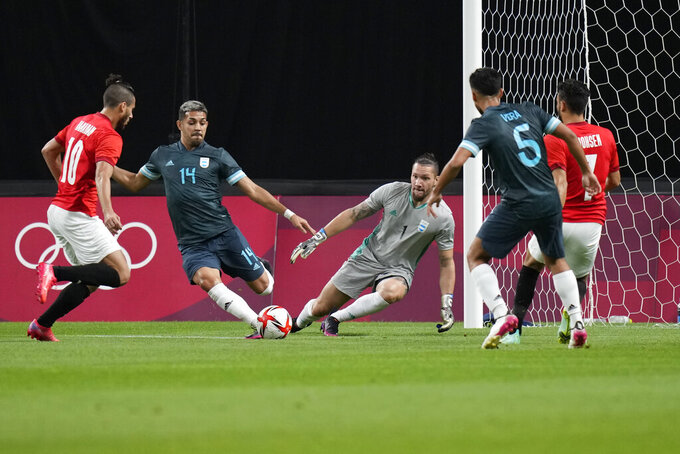 Argentina's Facundo Medina (14) clears the ball during a men's soccer match against Egypt at the 2020 Summer Olympics, Sunday, July 25, 2021, in Sapporo, Japan. (AP Photo/Silvia Izquierdo)