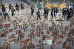 Protesters walk past barricades of bricks on a road near the Hong Kong Polytechnic University in Hong Kong, Thursday, Nov. 14, 2019. Hong Kong residents endured a fourth day of traffic snarls and mass transit disruptions Thursday as protesters closed some main roads and rail networks while police skirmished with militant students at major universities. (AP Photo/Kin Cheung)