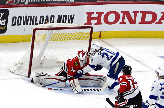 Chicago Blackhawks goaltender Kevin Lankinen (32) makes a save against Tampa Bay Lightning center Blake Coleman (20) during the second period of an NHL hockey game Sunday, March 7, 2021, in Chicago. (AP Photo/David Banks)
