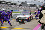 Denny Hamlin's pit crew runs onto pit road during a Hamlin pit stop in a NASCAR Cup Series auto race at Charlotte Motor Speedway in Concord, N.C., Sunday, Oct. 11, 2020. (AP Photo/Nell Redmond)