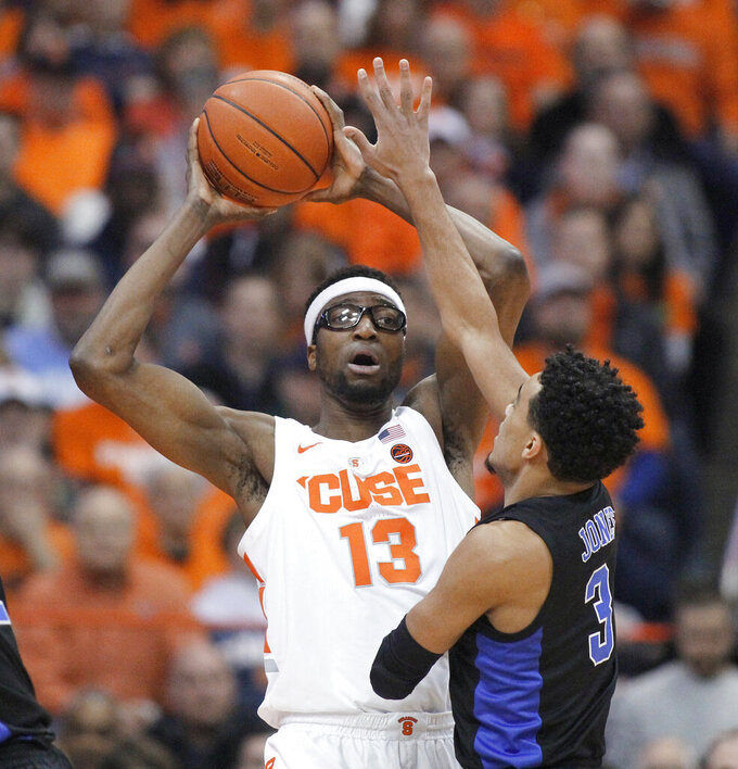 Syracuse's Paschal Chukwu, right, tries to pass the ball over Duke's Tre Jones, right, during the first half of an NCAA college basketball game in Syracuse, N.Y., Saturday, Feb. 23, 2019. (AP Photo/Nick Lisi)