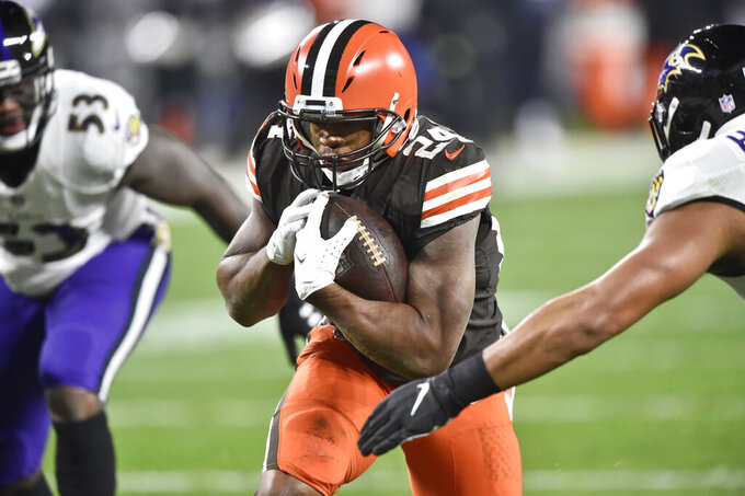Cleveland Browns running back Nick Chubb (24) rushes for a 7-yard touchdown during the first half of an NFL football game against the Baltimore Ravens, Monday, Dec. 14, 2020, in Cleveland. (AP Photo/David Richard)
