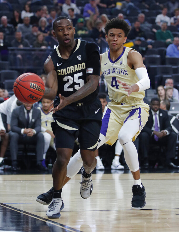Colorado's McKinley Wright IV passes around Washington's Matisse Thybulle during the first half of an NCAA college basketball game in the semifinals of the Pac-12 men's tournament Friday, March 15, 2019, in Las Vegas. (AP Photo/John Locher)