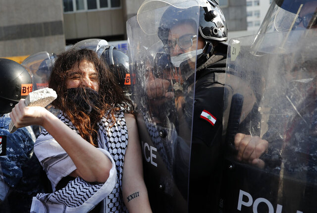 An anti-government protester confronts police with a stone during a protest against the deepening financial crisis, in Beirut, Lebanon, Tuesday, April 28, 2020. Hundreds of protesters set fire to two banks and hurled stones at soldiers, who responded with tear gas and batons in renewed clashes triggered by an economic crisis spiraling out of control amid a weeks-long virus lockdown. (AP Photo/Hussein Malla)