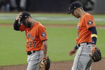Houston Astros second baseman Jose Altuve (27) and Carlos Correa react after Tampa Bay Rays' Mike Zunino's home run during the second inning in Game 7 of a baseball American League Championship Series, Saturday, Oct. 17, 2020, in San Diego. (AP Photo/Jae C. Hong)