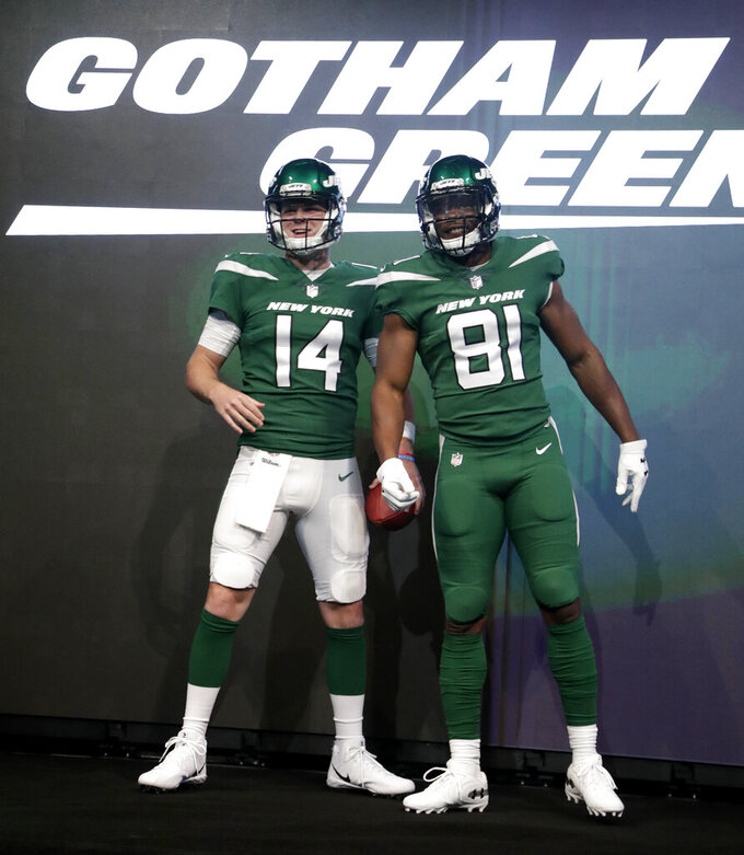 "New York Jets quarterback Sam Darnold (14) and wide receiver Quincy Enunwa (81) model the NFL football team's new ""Gotham green"" uniforms Thursday, April 4, 2019, in New York. (AP Photo/Julio Cortez)"
