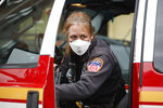 An FDNY medical worker wears personal protective equipment outside a COVID-19 testing site at Elmhurst Hospital Center, Wednesday, March 25, 2020, in New York. Gov. Andrew Cuomo sounded his most dire warning yet about the coronavirus pandemic Tuesday, saying the infection rate in New York is accelerating and the state could be as close as two weeks away from a crisis that sees 40,000 people in intensive care. Such a surge would overwhelm hospitals, which now have just 3,000 intensive care unit beds statewide. (AP Photo/John Minchillo)