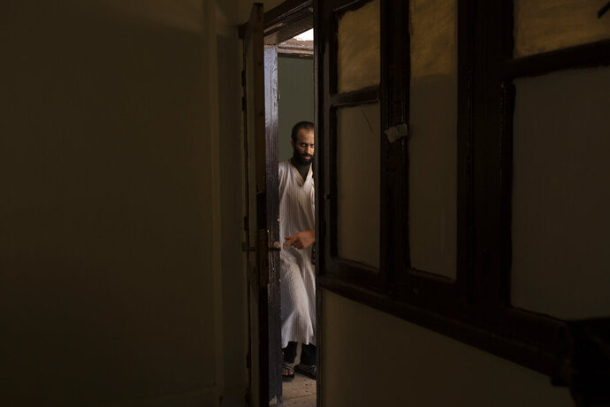 In this Sept. 4, 2019 photo, Abdul-Rahman al-Shmary, a Saudi Islamic State member who traded in Yazidi slaves and has been in a Syrian Kurdish-run prison since 2017, is led by guards to an interview in Rmeilan, northeast Syria. He dismissed the IS rules on slavery as rooted not in Islamic law but in the leadership's need for control.