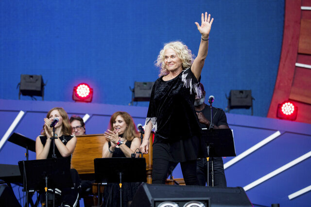 "FILE - In this Sept. 28, 2019, file photo, Carole King waves to the crowd as she takes the stage at the 2019 Global Citizen Festival in New York. Poised over the piano, King was set to play ""I Feel the Earth Move"" during a recent virtual fundraiser for Joe Biden when the Democratic presidential nominee himself beat her to it. ""On my playlist, Carole!"" Biden proclaimed, holding up his phone and letting a few seconds of the song blast.(AP Photo/Julius Constantine Motal, File)"