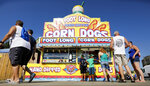 FILE - In this Aug. 9, 2018 file photo, Iowa State fairgoers line up to get a corn dog at a concession stand during the opening day of the Iowa State Fair in Des Moines, Iowa. With coronavirus cases rising throughout Iowa and around the nation, health experts are becoming increasingly worried about next month's Iowa State Fair, which will bring more than 1 million people to Des Moines. (AP Photo/Charlie Neibergall, File)