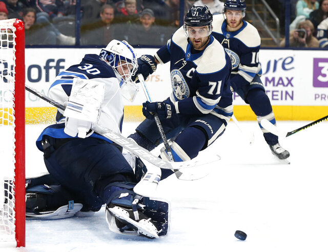 Winnipeg Jets' Laurent Brossoit, left, makes a save against Columbus Blue Jackets' Nick Foligno during the second period of an NHL hockey game Wednesday, Jan. 22, 2020, in Columbus, Ohio. (AP Photo/Jay LaPrete)
