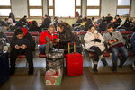 Travelers sit in waiting room at the Beijing Railway Station in Beijing, Friday, Jan. 17, 2020. As the Lunar New Year approached, Chinese travelers flocked to train stations and airports Friday to take part in a nationwide ritual: the world's biggest annual human migration. (AP Photo/Mark Schiefelbein)