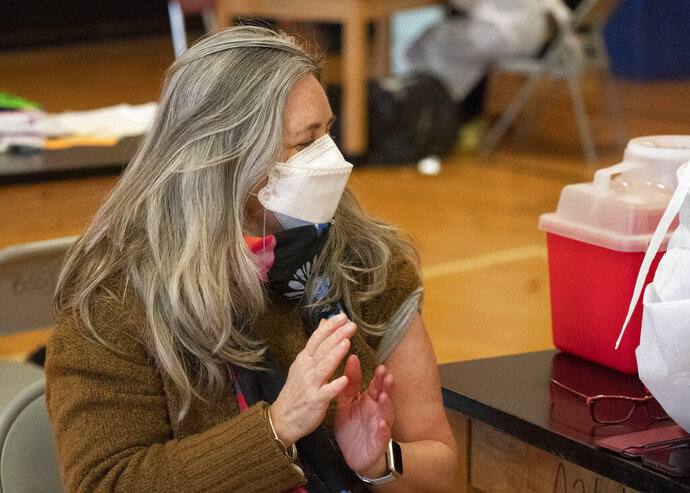 Teacher Lisa Egan claps after she receives the Moderna coronavirus vaccine at a clinic organized by New York City's Department of Health, Monday, Jan. 11, 2021.