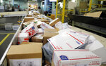 """FILE- In this Dec. 14, 2017, file photo, packages travel on a conveyor belt for sorting at the main post office in Omaha, Neb. The city of New York and the state of California sued the U.S. Postal Service Tuesday, Oct. 22, 2019, to stop tens of thousands of cigarette packages from being mailed from foreign countries to U.S. residents, saying the smugglers are engaging in """"cigarette tax evasion"""" while postal workers look the other way.  (AP Photo/Nati Harnik, File)"""