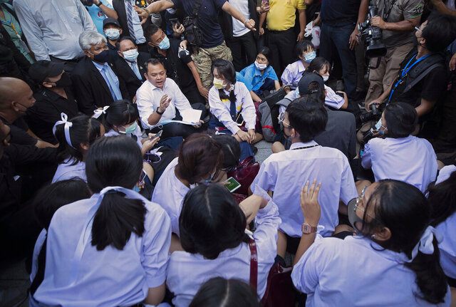 In this Aug. 19, 2020, file photo, Education Minister Nataphol Teepsuwan, center left in white shirt, talks to pro-democracy self-named