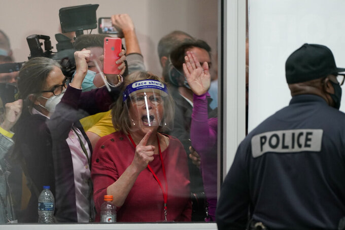 FILE - In this Wednesday, Nov. 4, 2020, file photo, election challengers yell as they look through the windows of the central counting board as police were helping to keep additional challengers from entering due to overcrowding, in Detroit. There is no shortage of job openings for election officials in Michigan. And Pennsylvania. And Wisconsin. After facing waves of threats and intimidation during the 2020 election and its aftermath, county officials who run elections are quitting or retiring early as the once quiet job has become a minefield because of the baseless claims of fraud pushed by former President Donald Trump and much of the Republican Party. (AP Photo/Carlos Osorio, File)
