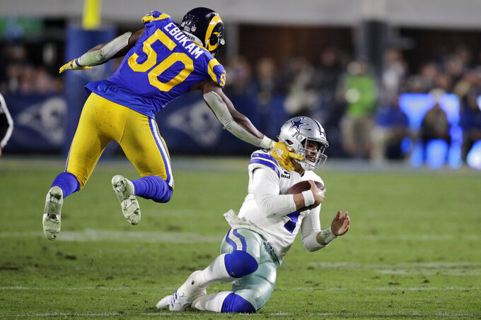 Dallas Cowboys quarterback Dak Prescott goes to the ground in front of Los Angeles Rams outside linebacker Samson Ebukam during the second half in an NFL divisional football playoff game Saturday, Jan. 12, 2019, in Los Angeles. (AP Photo/Jae C. Hong)