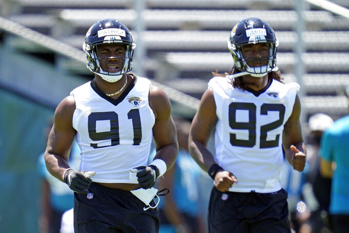 Jacksonville Jaguars defensive end Aaron Patrick (91) and defensive end Jordan Smith (92) warm up during an NFL football rookie minicamp, Saturday, May 15, 2021, in Jacksonville, Fla. (AP Photo/John Raoux)