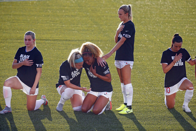 FILE - In this June 27, 2020, file phohto, Chicago Red Stars' Julie Ertz, second from left, holds Casey Short, center, while other players for the team kneel during the national anthem before an NWSL Challenge Cup soccer match against the Washington Spirit at Zions Bank Stadium in Herriman, Utah. The National Women's Soccer League revised its anthem policy after most players knelt during the anthem before season-opening games last weekend at the Challenge Cup. (AP Photo/Rick Bowmer, File)