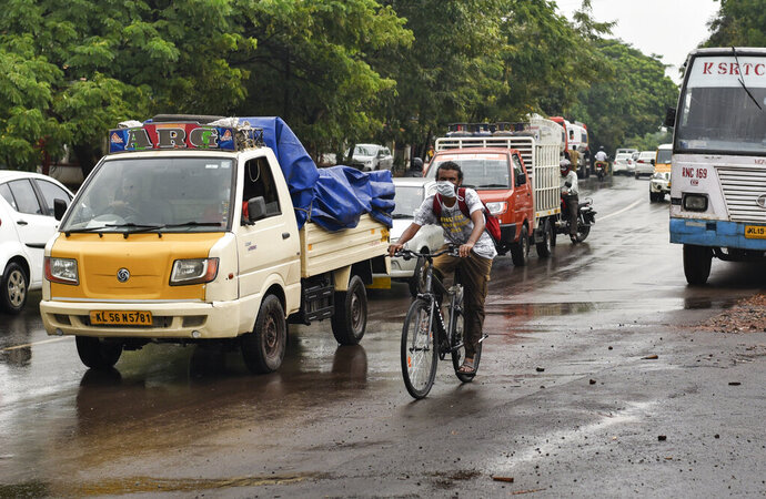 A cyclist wearing a mask pedals past other vehicles during extended lockdown in Kochi, southern Kerala state, India, Monday, May 18, 2020. India on Monday saw a slow trickle of people returning outdoors and thin traffic on its roads in some states, a day after the federal government extended the nationwide coronavirus lockdown to May 31 but eased many restrictions to restore economic activity. (AP Photo/R S Iyer)