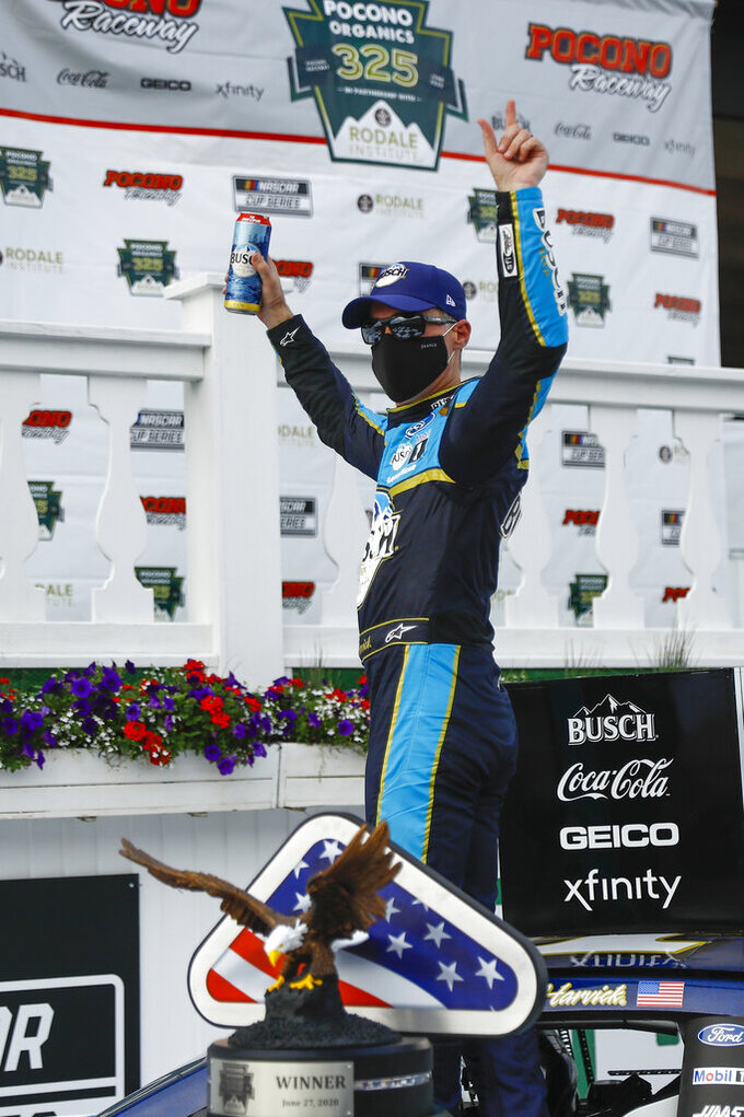 Kevin Harvick celebrates in the winners circle after winning the NASCAR Cup Series auto race at Pocono Raceway, Saturday, June 27, 2020, in Long Pond, Pa. (AP Photo/Matt Slocum)