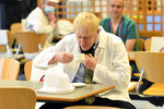 Britain's Prime Minister Boris Johnson drinks tea in the canteen during a visit to Royal Berkshire Hospital, Reading, England, Monday Oct. 26, 2020, to mark the publication of a new review into hospital food. (Jeremy Selwyn/Pool via AP)