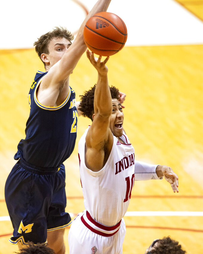 Indiana guard Rob Phinisee (10) drives to the basket with the ball as Michigan guard Franz Wagner (21) attempts to block his shot during the second half of an NCAA college basketball game, Saturday, Feb. 27, 2021, in Bloomington, Ind.  (AP Photo/Doug McSchooler)