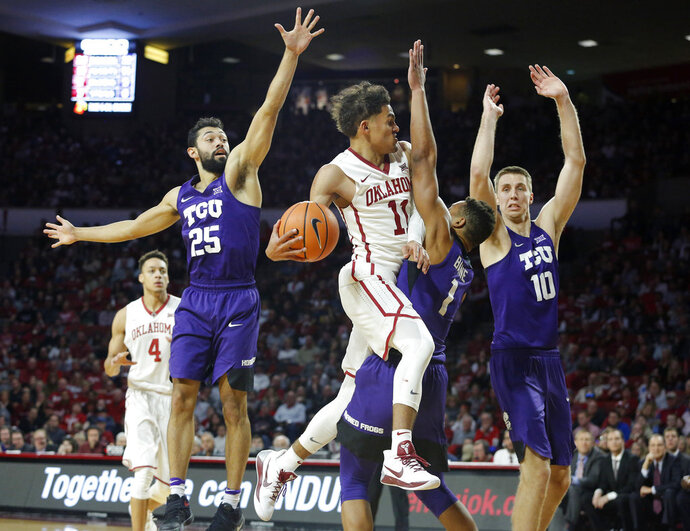 Oklahoma's Trae Young (11) goes up against TCU's Desmond Bane (1), Alex Robinson (25) and Vladimir Brodziansky (10) during the second half of an NCAA college basketball game in Norman, Okla., Saturday, Jan. 13, 2018. (AP Photo/Garett Fisbeck)