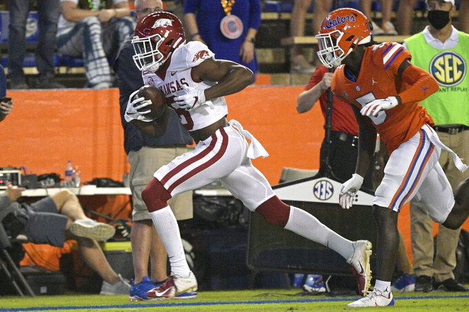 Arkansas wide receiver Mike Woods (8) scores a touchdown on a 47-yard pass play in front of Florida defensive back Kaiir Elam (5) during the first half of an NCAA college football game, Saturday, Nov. 14, 2020, in Gainesville, Fla. (AP Photo/Phelan M. Ebenhack)