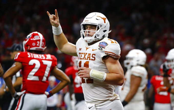 "FILE - In this Tuesday, Jan. 1, 2019 file photo, Texas quarterback Sam Ehlinger (11) celebrates his second touchdown carry in the first half of the Sugar Bowl NCAA college football game against Georgia in New Orleans. The hits came at Sam Ehlinger from just about every angle this summer. Baker Mayfield jabbed him first. Then Terry Bradshaw landed one. Texas' junior quarterback didn't seem to mind, and will likely care even less every time he gets to flash a ""Hook'em horns"" hand sign after scoring a touchdown. Which he does a lot. Ehlinger and the Longhorns are expected to again challenge for the Big 12 title in 2019. (AP Photo/Butch Dill, File)"