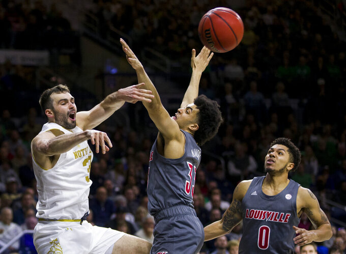Notre Dame's John Mooney, left, passes around Louisville's Jordan Nwora (33) and Lamarr Kimble (0) during the second half of an NCAA college basketball game Saturday, Jan. 11, 2020, in South Bend, Ind. Louisville won 67-64. (AP Photo/Robert Franklin)